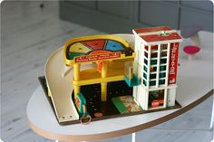 OHH... here it is, the Fisher Price garage that my brother and I spent hours playing with! The elevator has an up-crank that dings on every floor. The car can exit on the 3rd floor and zoom down the ramp. ZOOM!