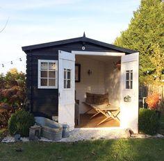 Un joli abri de jardin en bois entièrement repeint en noir et transformé en chambre d'amis ou salon de repos au fond du jardin.