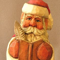 Santa Claus With Quill Pen and Open Book, Santa is ready to take names and record his naughty or nice list. He is carved in basswood and is wearing a red coat with white trim, and gold sash. He is finished with wax to protect the wood. He is 6.5 inches tall by 2.5 inches wide and 2.5 inches deep. He is getting ready for another busy Christmas Eve delivery by checking his list once and twice. Original Woodcarving by Russell Scott,   SA31