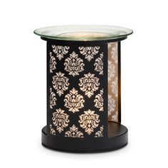 "Forbidden Fragrance Warmer  P91661    $30.00  Ornate damask motif shimmers with light while scenting your space. Heat from a tealight releases the fragrance of Scent Plus® Melts placed in the glass dish. Melts and tealight sold separately. Metal base features photo-etched panels backed with light-diffusing mesh; glass tealight cup. Specialty packaging. 5""h, 4¾""w. Universal Tealight® Candle	Scent Plus® Melts"