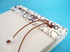 Bloco para recados feito em cartonagem, 80 folhas (15 X 21 cm) amarradas com cordão na parte superior. Revestidos com papéis especiais, acabamento em ilhós. As folhas podem ser repostas quando terminarem. OPCIONAL: As folhas podem ser feitas em dois tipos de papel: * Reciclato 75 gr; * Alta alvura (sulfite branco) 75 gr. R$ 22,90