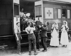 Medical orderlies watched by two nurses lift a stretcher-case, wounded in the capture of Hill 70, on to a train departing from a Casualty Clearing Station. 1917-09-15