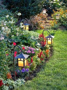 Solar lanterns at edge of curved garden