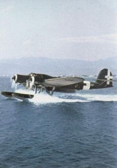 An Regia Aeronautica's float plane Cant-Z.506B Airone taking off from an air hairbor. Unit and location unknown. Photo taken in late war, note the dark blue-grey livery of the plane.