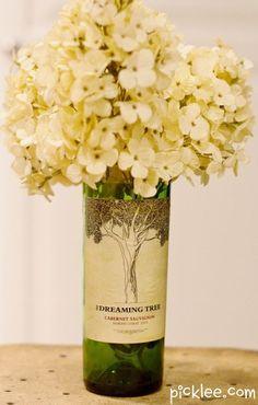 Une bouteille de vin utilisé comme une vase de fleurs