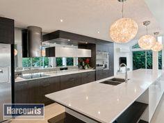 Gourmet kitchen with flawless mirrored splashback.