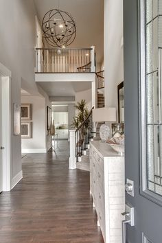The Rosario's spacious Two Story Foyer with an Elegant Chandelier and Beautiful Curved Staircase is Sure to Impress. By American Classic Homes. Entryway Stairs, Entryway Decor, Foyer Design, House Design, Wall Design, Foyer Paint, Two Story Foyer, Entryway Lighting, Elegant Chandeliers