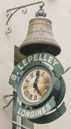 CHARENTON LE PONT -   Enseigne d'horloger  Adresse : 14, rue de Paris, Charenton-le-Pont, France  DatationXIXe siècle  L'enseigne d'horloger, qui aujourd'hui surplombe un magasin de prêt à porter, figure déjà sur les cartes postales de la fin du siècle dernier.