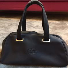 Lacoste bag - bowling bag style Excellent condition - black PVC - discreet Lacoste logo - very light and practical - classical bowling bag fashion Lacoste Bags Totes