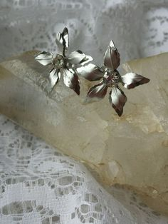For sale is a lovely pair of signed Bugbee And Niles Poinsettia Screw back Earrings. Measuring 1 inch in diameter these earrings consists of a single clear prong set rhinestone in the center surrounded by rhodium plated leaves in a matte and shiny finish. Vintage jewelry will show some signs of wear but these are in excellent condition. Please look at the pictures carefully as they are part of the description. I only use EBay's Global Shipping for international buyers. I can combine s...