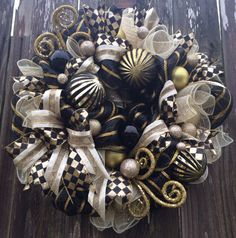 Christmas Wreath, Black & Gold Wreath, Black & Gold Decor, Christmas Decor Dazzling in Black & Gold is this Stunning wreath in High Fashion Design! This is a WOW - a statement piece- a stand back and take a long look - cause this wreath is Lush! Made on a pine base and filled with black & gold stripped mesh, cream white & gold basket weave mesh ruffles, beautiful bold ribbon patterns, gorgeous ornaments, sprays of gold leaves and ornament balls. Measures 25 inches and ready to ship