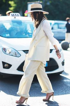A white blouse is worn with a pantsuit, heels, and a straw hat