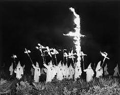 klu klux klan doing rituals and burning the christian cross.