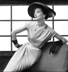 1952 Marie-Thérèse in pale pink pleated shantung which follows the asymmetrical line of the neck and in the skirt by Nina Ricci, wide-brimmed straw hat by Claude St. Cyr, photo by Pottier