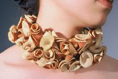 Mary Donald studied at San Diego State University, where she focussed on Metalsmithing & Jewellery Design. She uses various materials such as wood, rubber, plastics, latex, fibre, metal and unusual found objects to make her unconventional jewellery pieces. -  piece using orange peel and thread.