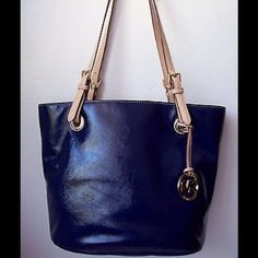 """MIchael Kors Navy Blue Leather Tote, Gold Hardware Gold MK medallion hangs off front strap, flat leather shoulder straps with Gold Buckles, Exterior Pocket, Inside lined in signature gold fabric, Back interior wall has large zip pocket & cell phone pocket. Bag Depth: 5.5"""", Bag Length: 11"""", bottom 14"""", Material - Leather, Strap Drop is 10"""", Height: 10.5"""" MICHAEL Michael Kors Bags Totes"""