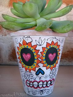 I am so painting my own. Candy skulls. Day of the Dead Planters