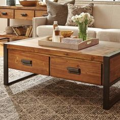 This roughly finished wood coffee table sits on a durable black metal frame. Two drawers on each side open for hidden storage and open with black metal pulls. This rustic coffee table is a warm accent                                                                                                                                                                                 More