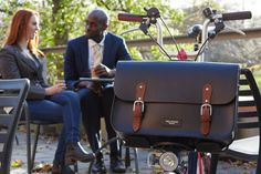 """ABOUT EARL  This bag cuts a dash in the city, as it has been perfectly created to  attach to the Brompton C Frame bag holder. Earl has been crafted in black  satchel leather with contrasting tan brown buckle straps,nickel plated  brass buckles and a silver embossed logo.This bag also comes with a  matching black leather shoulder strap so it is the perfect bag for the bike  to boardroom transformation.  Earl easily attaches to the """"C frame"""" and secures firmly with strong velcro  straps…"""