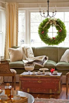 A classic holiday wreath looks beautiful hung in a cozy window niche - Traditional Home® Love this couch! Christmas Time Is Here, Christmas Love, All Things Christmas, Winter Christmas, Winter Holidays, Happy Holidays, Christmas Houses, Country Christmas, Christmas Trees