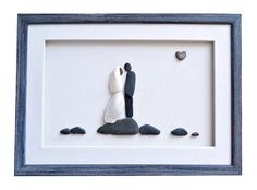 Unique wedding art, special love gift for the new family. This one of a kind pebble art is a perfect wedding gift idea. Newlyweds in a gentle embrace on the riverbank.  Pebbles are used on a canvas to create image of a groom and shells are used for image of a bride. A natural shaped heart beach stone is an expression of true love. Excellent choice for gift for any couple celebrating marriage, engagement or anniversary. The beautiful simplicity of the images and neutral tones of pebbles allow…