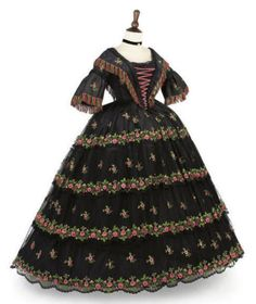 This late 1850s gown is of Spanish origin and mixes stylish 1850s fashion with two traditional Spanish costume features: black lace and bright colors.