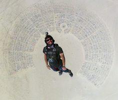 Fantastic shot of man skydiving into Burning Man...