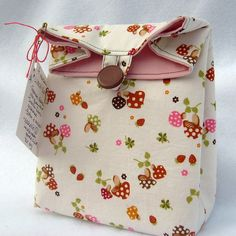 I found a nice tutorial for these little lunch sacks.  It's made from new and reclaimed fabrics, and a reclaimed button, as well.  I also made a reusable, removeable liner for the inside of the bag -- made from fused plastic bags.  I am hoping that will help prevent any leaks, and may help with insulation.  The bag is washable, too.