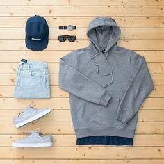 grey pullover hoodie. long navy tee. light wash denim. grey / white sneakers. navy 5-panel hat.