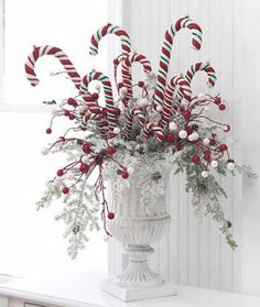 This is gorgeous!  Simple frosted greenery, red berries and faux candy canes create this beautiful Christmas centerpiece!