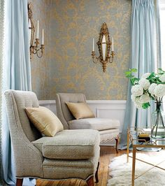 Subtle gold touches--the wallpaper, sconces, coffee table--enhance this blue & white room.
