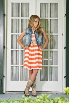 JuJu's having fun with mixing prints! Awesome peacock Corral boots with orange striped dress and denim vest.