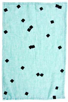 Floating Confetti Tea Towel: Hand-stamped blocks take on a confetti-like form, floating along a linen tea towel from Caroline Z Hurley.
