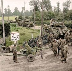 British Sherman tanks and 6-pdr anti-tank guns of the 11th Armoured Division, advancing through the village of Saint-Charles-de-Percy in Calvados, on the N 177 road to Vire. August 2, 1944. (N 177 - Vire - Mortain)