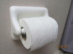 white ceramic or porcelain toilet paper roll holder