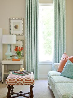 Note the perfect placement of the accent color (coral) in this space.  --From the shell of the room to the center ottoman.