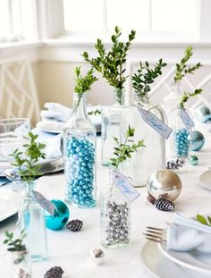 Line an all-white table with glass bottles filled with metallic beads or bells and topped with boxwood clippings. More Christmas centerpiece ideas: http://www.midwestliving.com/homes/seasonal-decorating/easy-christmas-centerpiece-ideas/?page=5