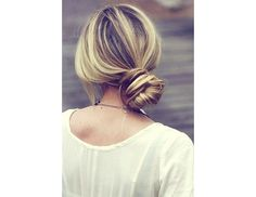 Knotted side bun. To create it, secure your hair with an elastic, split the pony in two, and then tie into a basic knot! Wrap the remaining hair around your bun and hold everything in place with bobby pins.