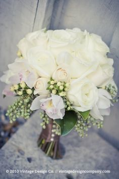 Love this classic white rose bouquet with accents of coffeeberry and cymbidium orchid blooms