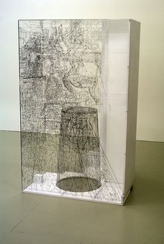 "Pia Linz ""...builds a plexiglas box construction... then sits inside her construction and captures with a felt marker in every direction around herself what she sees directly in detailed drawing on the transparent inner walls. After this, she renders the drawing permanent by engraving the lines into the plexiglas"""