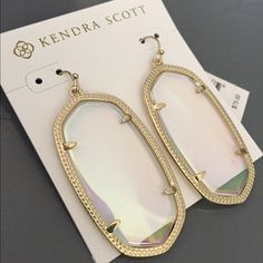 Iridescent Clear Kendra Scott Danielle Earrings I was so excited to have this pair, but they are just too big for me. They are gorgeous! Clear iridescent with gold metal. These tend to go more toward a light pink when light hits them :) I would love to trade for some other Kendra Scott. I believe this is a sold out color on their website. Kendra Scott Jewelry Earrings