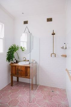 Scandinavian bathroom with patterned pink floor tile and walk-in shower