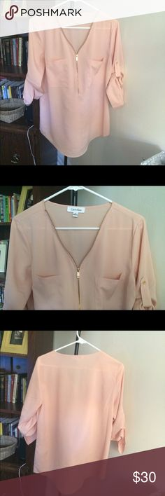 NWOT Size M Calvin Klein Blouse This Blouse is gorgeous and brand new without tags. Color just didn't work for my skin tone. Cute front zipper details and pockets and ability to button up to 3/4 length. It's somewhat sheer so I would suggest to wear an undershirt. Calvin Klein Tops Blouses
