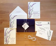 A wild little bouquet of lavender and rosemary adorn this wedding invitation. A dark purple pocketfold wraps around the wedding invitations and holds
