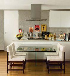 Para integrar a cozinha ao living desta cobertura dúplex de 70 m2, ela foi construída no andar de cima. A solução encontrada pelo arquiteto Gustavo Calazans para reunir os dois ambientes foi incluir uma mesa de vidro quadrada (1,40 x 1,40 m), que deu leveza e permitiu que o móvel ficasse encostado na bancada do cooktop. Pela proximidade da cozinha com o estar, Calazans decidiu não colocar tapete sob a mesa de jantar.