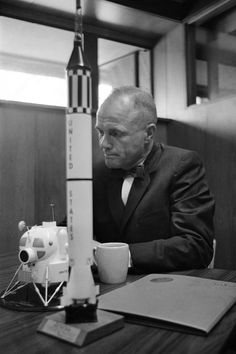 In 1963... In this February 8, 1963 file photo, astronaut John Glenn sits with models of the Mercury spacecraft atop its launch rocket and a lunar module, representing the past and the future of space exploration as he talks about the first anniversary of his historic flight. (Photo by AFP Photo)