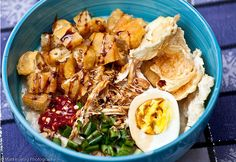 Bubur Ayam (Chicken Porridge) is a marriage of sweet soya sauce, spicy sambal, savory egg and chicken, and crunchy krupuk served on rice porridge. #Indonesianfood