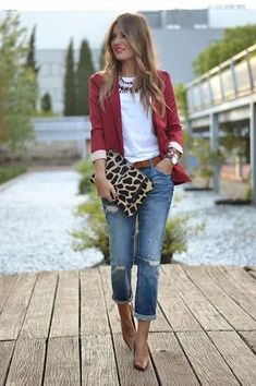 A nicely put together combination of a red blazer and blue distressed jeans will set you apart effortlessly. Brown leather pumps will bring a classic aesthetic to the ensemble.  Shop this look for $126:  http://lookastic.com/women/looks/necklace-crew-neck-t-shirt-belt-blazer-clutch-jeans-pumps/4949  — Burgundy Necklace  — White Crew-neck T-shirt  — Brown Leather Belt  — Red Blazer  — Tan Leopard Leather Clutch  — Blue Ripped Jeans  — Brown Leather Pumps