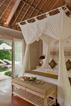 A canopied bed and pitched bamboo roof add to the romantic, tropical charm at Puri Sunia Resort #Indistay