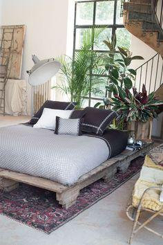 Une chambre à l'ambiance zen et relaxante avec un pied de lit en bois et une déco tropicale